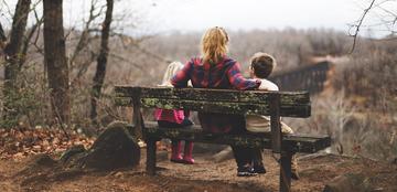 Woman sitting between two children on bench - rear view (Benjamin Manley on unsplash.com)